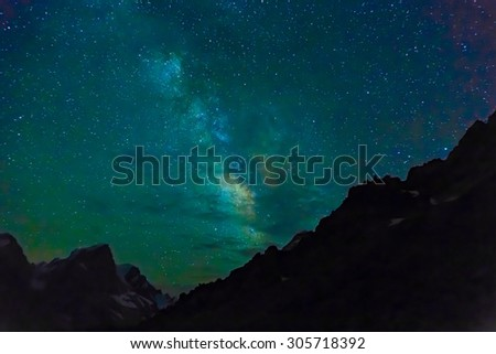 Night mountain landscape. Silhouettes of sharp rocky ridge shape mountain peaks and edges night sky with many stars and milky way on background - stock photo