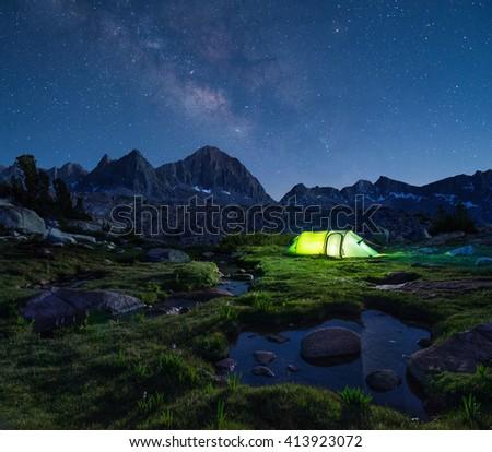 Night mountain landscape with illuminated tent. Mountain peaks and the milky way on horizon. - stock photo