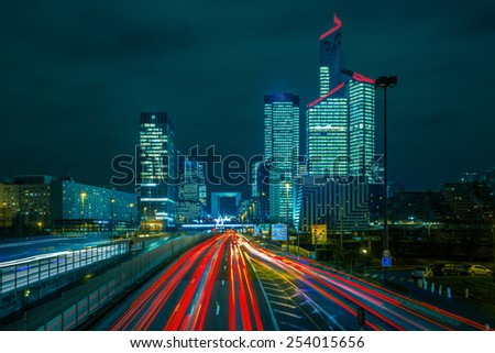 Night multi-lane road with skyscrapers of the La Defense, Paris, France. Long exposure. - stock photo