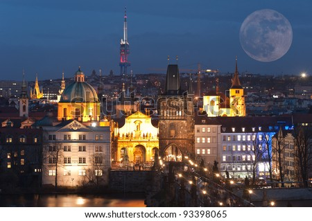 Night panorama with a big full moon of Prague old town with the Charles bridge and the modern Zizkov Tower behind, Czech Republic. Composite of multiple images - stock photo