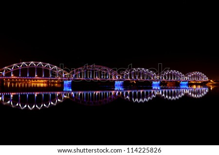 night panoramic scene with railway bridge in Riga, Latvia - stock photo