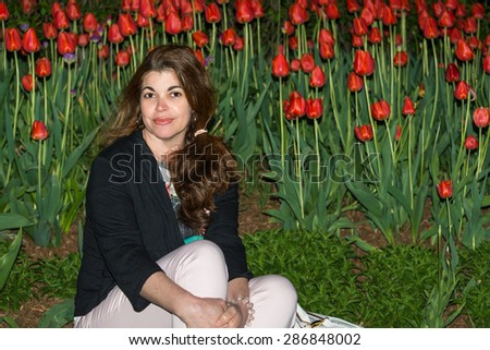 Night Portrait in tulip garden: Beautiful Hispanic woman sitting on the grass with flowering tulips - stock photo