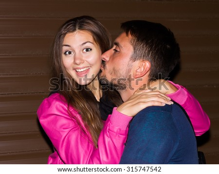 Night portrait of happy Couple at chocolate urban wall background.Portrait of cheerful and lovely couple.So happy. Beautiful young boyfriend with beard kissing girlfriend - stock photo