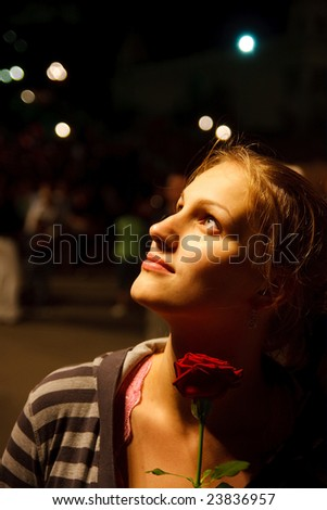Night portrait of woman holding red rose