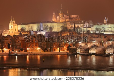 Night romantic snowy Prague gothic Castle and St. Nicholas' Cathedral with Charles Bridge, Czech republic - stock photo