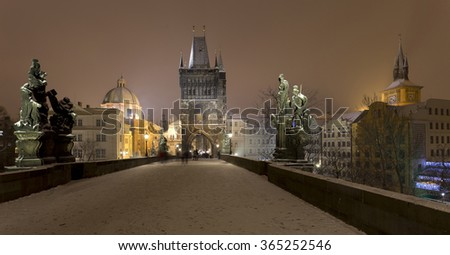 Night romantic snowy Prague Old Town with Bridge Tower and St. Francis of Assisi Cathedral from Charles Bridge with its baroque Statues, Czech republic - stock photo