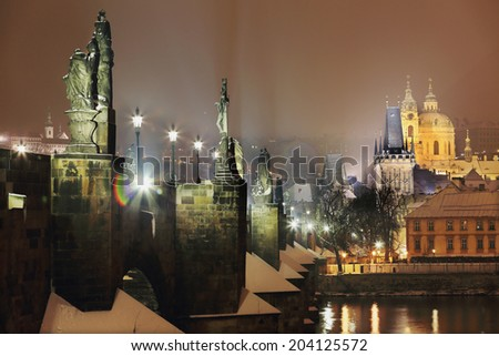 Night romantic snowy Prague St. Nicholas' Cathedral with Charles Bridge above River Vltava, Czech republic