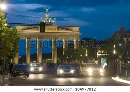 night scene Brandenburg Gate lit with car pedestrian traffic at night on Unter den Linden Berlin Germany Europe - stock photo