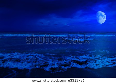 Night scene in a deserted beach with a crescent moon - stock photo