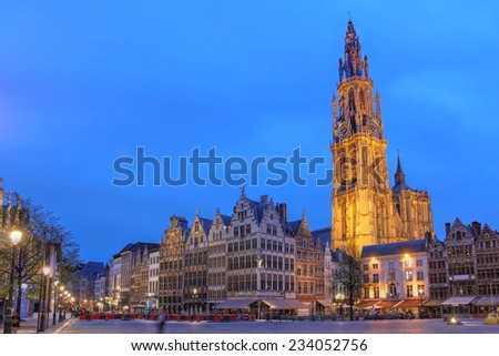 Night scene in downtown Antwerp, Belgium along the famous Meir Street and the lonely tower of the  Cathedral of our Lady. - stock photo