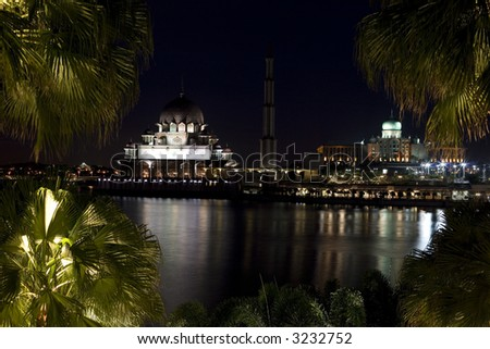 Night scene of a mosque bright lights reflected on the river - stock photo