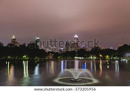Night scene of Bangkok skyline at dusk from Lumphini Park, Bangkok Thailand - stock photo