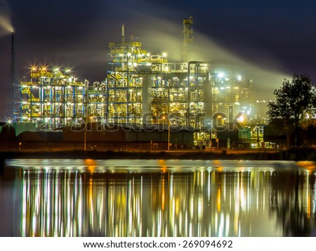 Night scene of detail of a heavy Chemical Industrial plant reflecting in water with mazework of pipes in twilight - stock photo