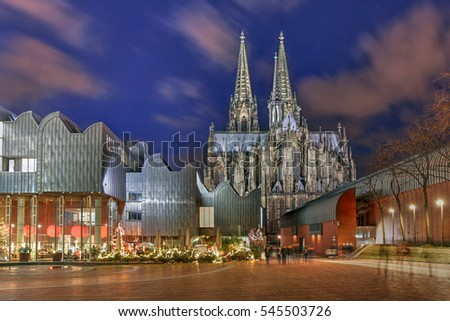Night scene of Heinrich-Boell square in Cologne, Germany with the Cologne Philarmonie Hall and the Ludwig Museum, overlooked by the majestic Cologne Cathedral.