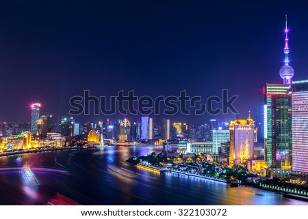 night scene of the city with a river around skyscrapers - stock photo