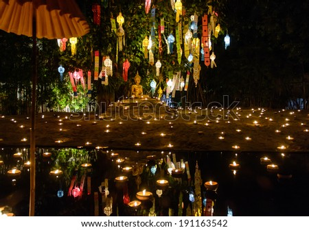 night scene . public A golden Buddha statue on a pool with lantern and candle deco for festival