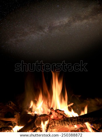 Night scene with fire under stars in sky - stock photo