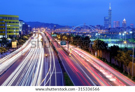 Night scenery of Taipei City with view of Taipei 101 Tower in downtown, MacArthur Bridge across river and car trails on Dike Avenue ~ Taipei cityscape at dusk by riverside (long exposure effect) - stock photo