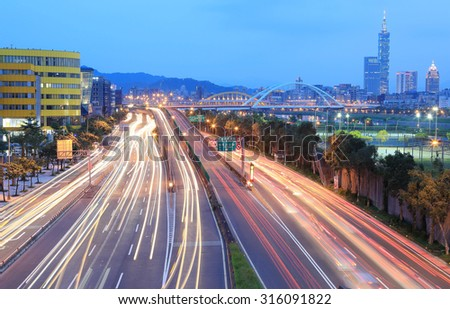 Night scenery of Taipei City, Xin-Yi District and downtown area with arch bridges and car trails on Dike Avenue during rush hour ~ Romantic cityscape of Taipei at dusk by riverside (long exposure) - stock photo