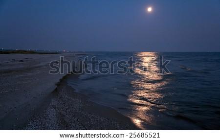 night sea sandy shore with full moon and moonlight path - stock photo