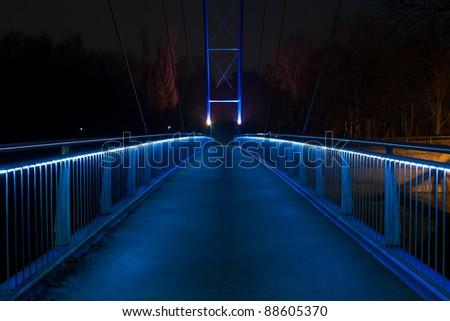 Night shot of a glowing blue footbridge - stock photo