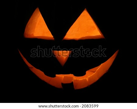 Night shot of carved pumpkin lit for Halloween. - stock photo