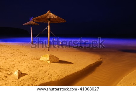 Night shot of Hawaiian raffia parasols on a sandy beach. - stock photo