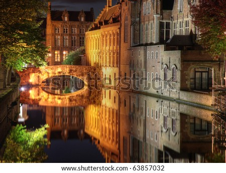 Night shot of historic medieval buildings along a canal in Bruges, Belgium, which is on the world heritage list of unesco - stock photo
