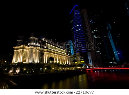 Night shot of hotels and tall buildings along the Singapore river brightly lit - stock photo