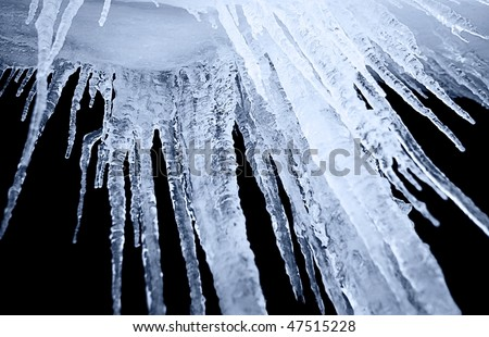 night shot of icicle on a black background - stock photo