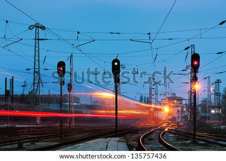 Night shot of railway station with curving track and passing train - stock photo