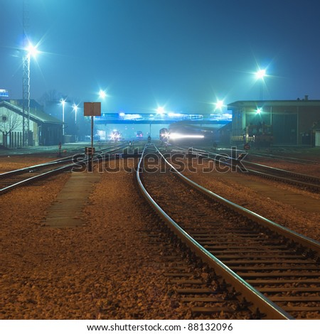 Night shot of railway station with curving track and passing train in background