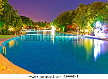 Night shot of the swimming pool at the caribbean resort. Mexico. - stock photo