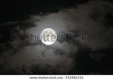 Night sky and a full moon in the clouds - stock photo