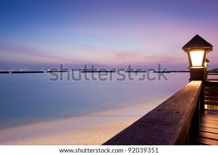 Night sky at a seaside beach resort with sun setting, long exposure - stock photo