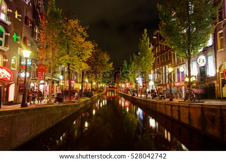 Night spirit view in Amsterdam. Beautiful canals with many people and little coffee shops and bars by the sides. Golden autumn in Netherlands.