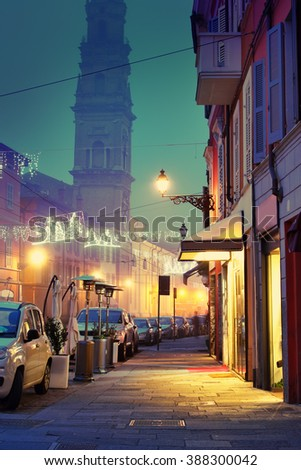 Night street illuminated with lamps in the town of Parma, Emilia Romagna, Italy. - stock photo