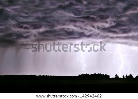 Night thunderstorm,rain,lightning,in the field of the forest. - stock photo