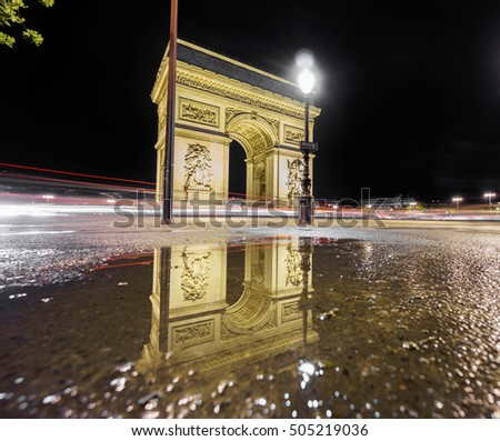 Night time in Arc de Triomphe and reflection over water pond