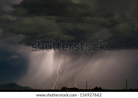 Night time thunderstorm at work with a coupe of ground strikes. Image was shot at high iso and does have noise present. - stock photo