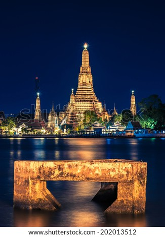 Night time view of Wat Arun (Temple)  across Chao Phraya River and concrete in foreground in Bangkok, Thailand. - stock photo