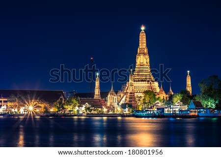 Night time view of Wat Arun (Temple)  across Chao Phraya River in Bangkok, Thailand. - stock photo