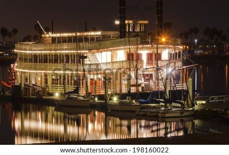 Night view of an authentic,vintage,American riverboat with two chimneys resembling the steamboats used in 1800s in Mississippi river. A view of Mission Bay and pier,San Diego,southern California,USA. - stock photo