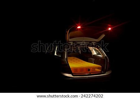 Night view of an illuminated open car boot on an estate car or station wagon with a mattress inside - stock photo