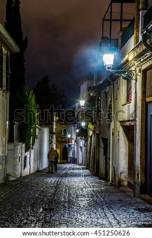 night view of an illuminated street in the historical center of the spanish city granada