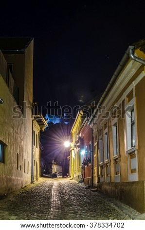 night view of an illuminated street inside of the citadel of romanian city sighisoara - stock photo