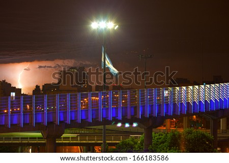 night view of buenos aires in the rain,	 lightning and the Argentine flag