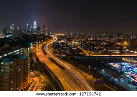 Night view of elevated busy highway heading towards Kuala Lumpur city in Malaysia - stock photo