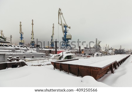 Night view of harbor cranes on the waterfront of the port covered with snow.  - stock photo