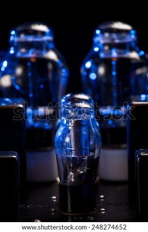 Night view of hi fi amplifier with electronic vacuum tubes with incandescent filament. Grazing blue light and bokeh background - stock photo